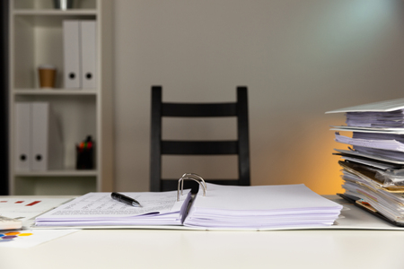 Empty office with colorful wall and folders on table.