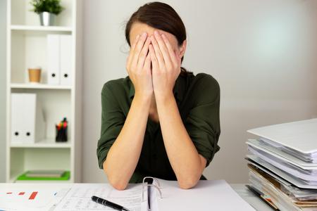 Businesswomen hiding behind her hands in an office. Business finance concept. Stock Photo