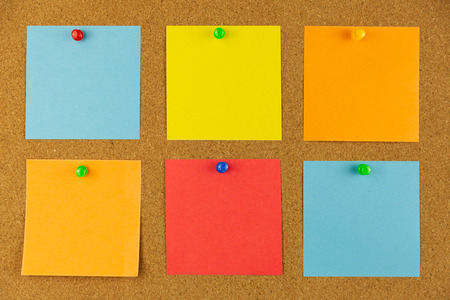 Colorful paper pined to cork board as reminders.