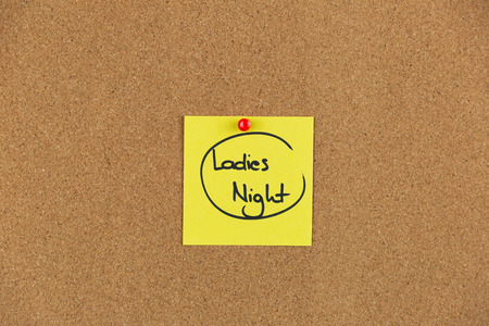 Note on a cork board with writing ladies night out. Stock Photo
