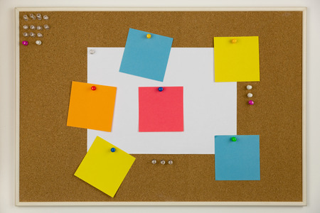 Cork board with pins and papers with reminders and tasks. Stock Photo
