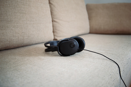 Headphones on a sofa in a living room. Stock Photo