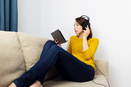 Beautiful women sitting in sofa and listening with headphones. E-learning concept.