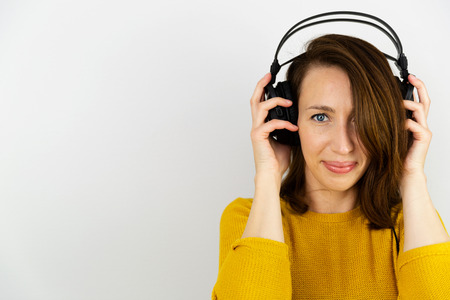 Beautiful women listening with headphones on a white background. Stock Photo