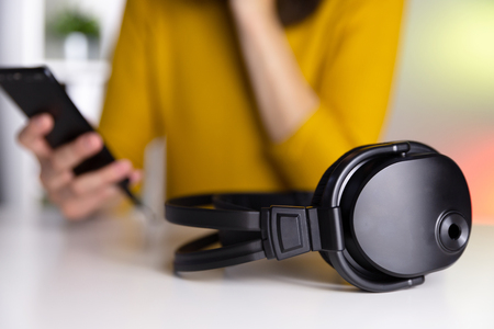 Headphones on a table with colorful background and a women with a smart phone in her hands.