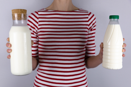Zero waste concept. Beautiful women holding in hands a glass reusable bottle of milk and in other hand plastic bottle.