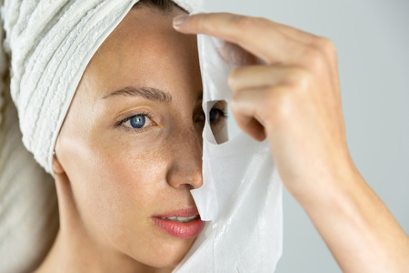 Beautiful women applying facial mask with moisturizer Stock Photo