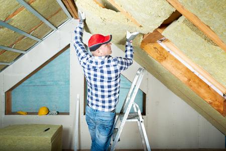 Mann, der thermische Dachisolationsschicht installiert - unter Verwendung von Mineralwolleplatten. Dachgeschoss Renovierungs- und Dämmkonzept
