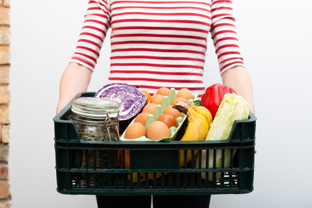 Woman holding box of grocery food and from store. Online grocery shopping service concept