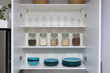 Various seeds in storage jars in pantry, white modern kitchen in background. Smart kitchen organization Stock fotó
