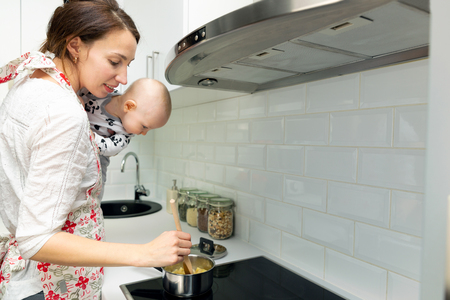 Young mother with a baby on her hands cooks the food in a pot on the stove Stock Photo