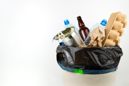 Plastic, glass, metal and paper garbage in black garbage bag for recycling concept reuse and recycle