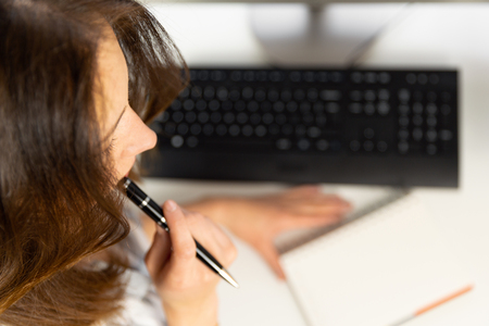 Young woman manager sitting and thinking in workspace with computer and notebook