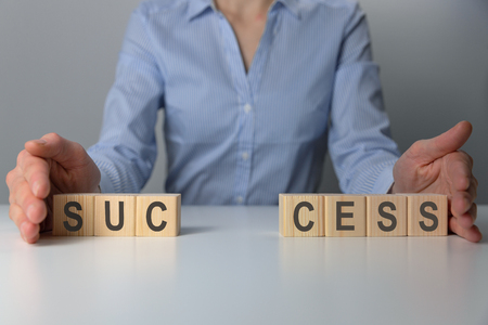 Businesswoman adjusting success word made of wooden blocks. Success word from wooden blocks on desk. Business success