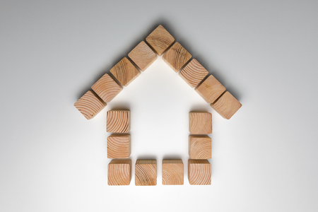 House of natural colored toy blocks on white background. House building concept