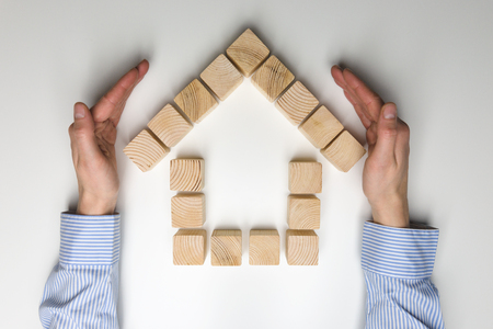 House of wooden blocks. Wooden toy house protected by womans hands. The concept of home protection Stock Photo