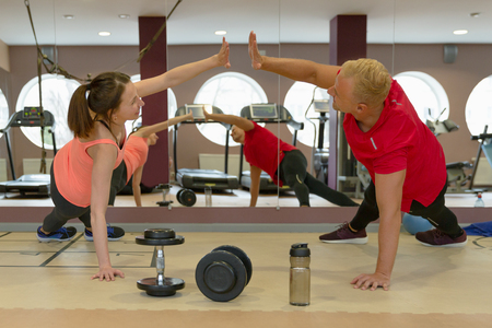 Fitness parners in sportswear doing exercises at gym. Fitness sport gym concept