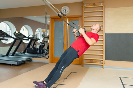 Man exercising with suspension training trx. Total body resistance exercises
