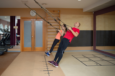 Fitness partners, sports people are working out with TRX in gym. Total body resistance exercises