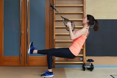 Woman exercising with suspension training trx. Total body resistance exercises