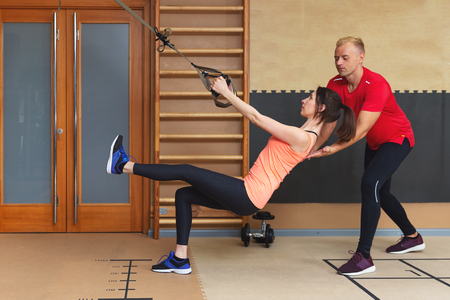 Young woman exercising with trx gym equipment with personal trainer helping. Total body resistance exercises