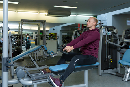Man training in a gym. Fit young man in sportswear working out alone in a gym