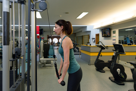 Young fitness woman doing triceps exercises in the gym Stock Photo