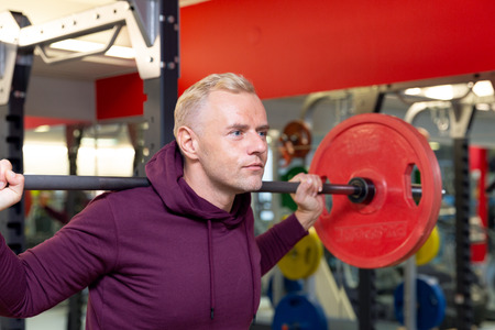Young man lifting heavy weights during a workout session. Man training with barbell
