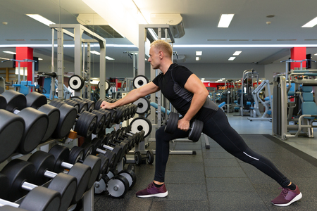 Young man doing the exercises with dumbbell at biceps for good body in fitness gym, bodybuilder, healthy lifestyle, exercise fitness, workout and sport training concept Stock Photo