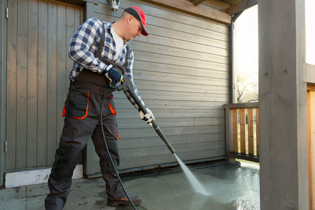 Man is cleaning terrace with a high temperature pressure cleaner on concrete terrace floor