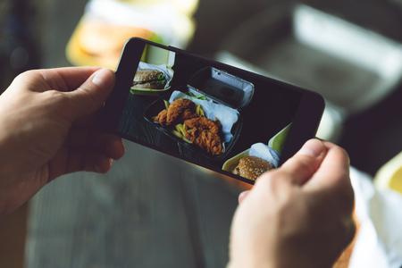 Robienie zdjęć hamburgera, frytek i smażonego kurczaka w pojemnikach na wynos za pomocą smartfona. Dostawa jedzenia, koncepcja fast foodów i blogerów kulinarnych