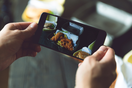 Taking photo of hamburger, french fries and fried chicken in takeaway containers with smart phone. Food delivery, fast food and food blogger concept
