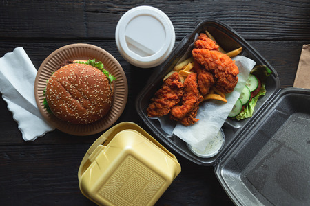 Hamburger, french fries and fried chicken in takeaway containers on the wooden background. Food delivery and fast food concept