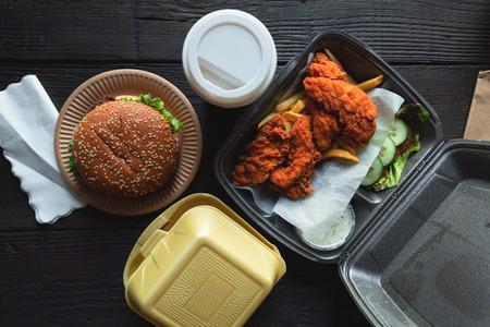 Hamburger, patatine fritte e pollo fritto in contenitori da asporto sullo sfondo di legno. Consegna del cibo e concetto di fast food Archivio Fotografico
