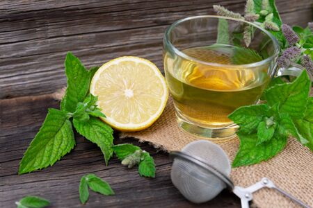 Hot peppermint tea with lemon on wooden background