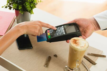 Customer making payment using credit card.Waiter holding credit card swipe machine while customer typing PIN code