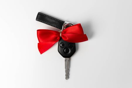 Car keys with red bow as present on white background. New car gift concept