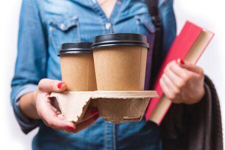 Dos tazas de café de papel para llevar en la mano de una mujer. Estudiante con tazas de café para llevar y libro en sus manos