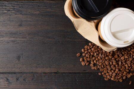 Dos tazas de papel de café en un portavasos y granos de café en la mesa de madera oscura. Café de buena calidad Foto de archivo