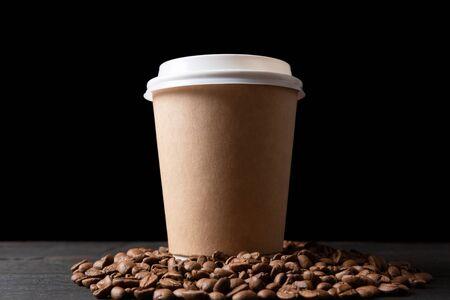 Tazza di carta di caffè e chicchi di caffè sul tavolo di legno scuro. Caffè di buona qualità