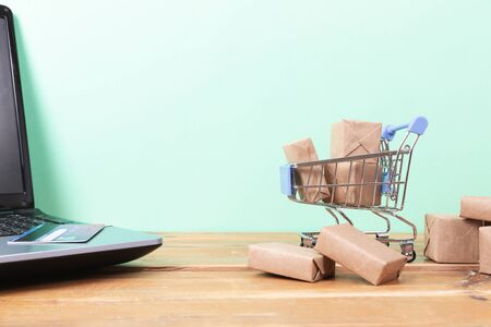 Online shopping concept. Shopping cart, small boxes, laptop and credit card on the desk Imagens