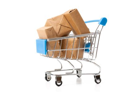 Online shopping concept. Shopping cart with small boxes inside on white background
