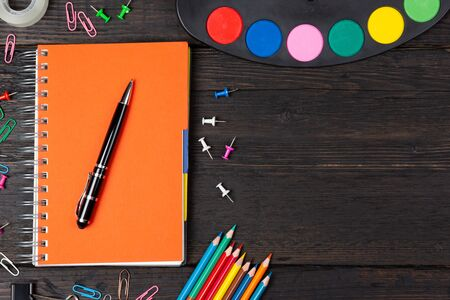 School stationery supplies and watercolors on dark background. Back to school concept