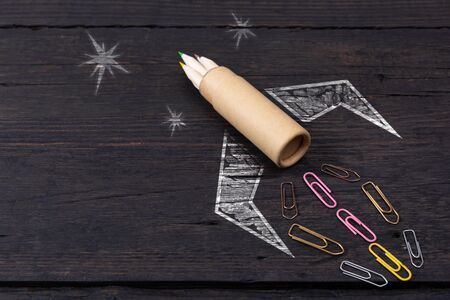 School stationery supplies and hand drawn rocket ship on dark background. Back to school concept. New idea and creativity launching