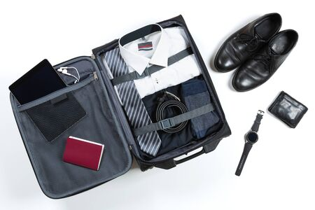 Business, trip, luggage and people concept. Business formal wear clothes packed into travel bag 免版税图像