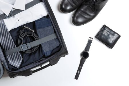 Business, trip, luggage and people concept. Business formal wear clothes packed into travel bag Banco de Imagens