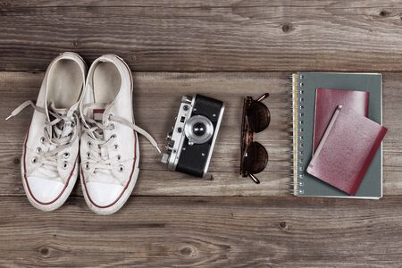 Essentials for modern young person travel. Sneakers, camera, sunglasses, notebook, passport and hat. Easy travel