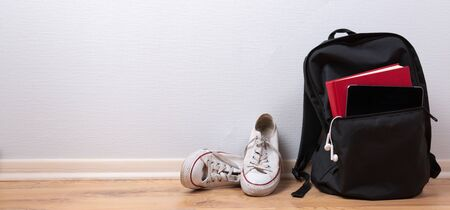 Old white sneakers, book and tablet with earphones in backpack on wooden background. School and student travel concept