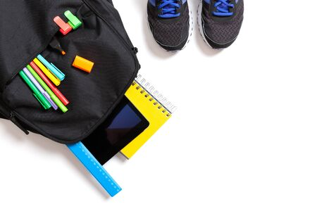 Back to school concept. Backpack with school supplies, tablet and sport sneakers