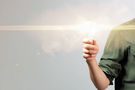 Business woman hand holding lightbulb in office. Concept saving energy, idean and creativity
